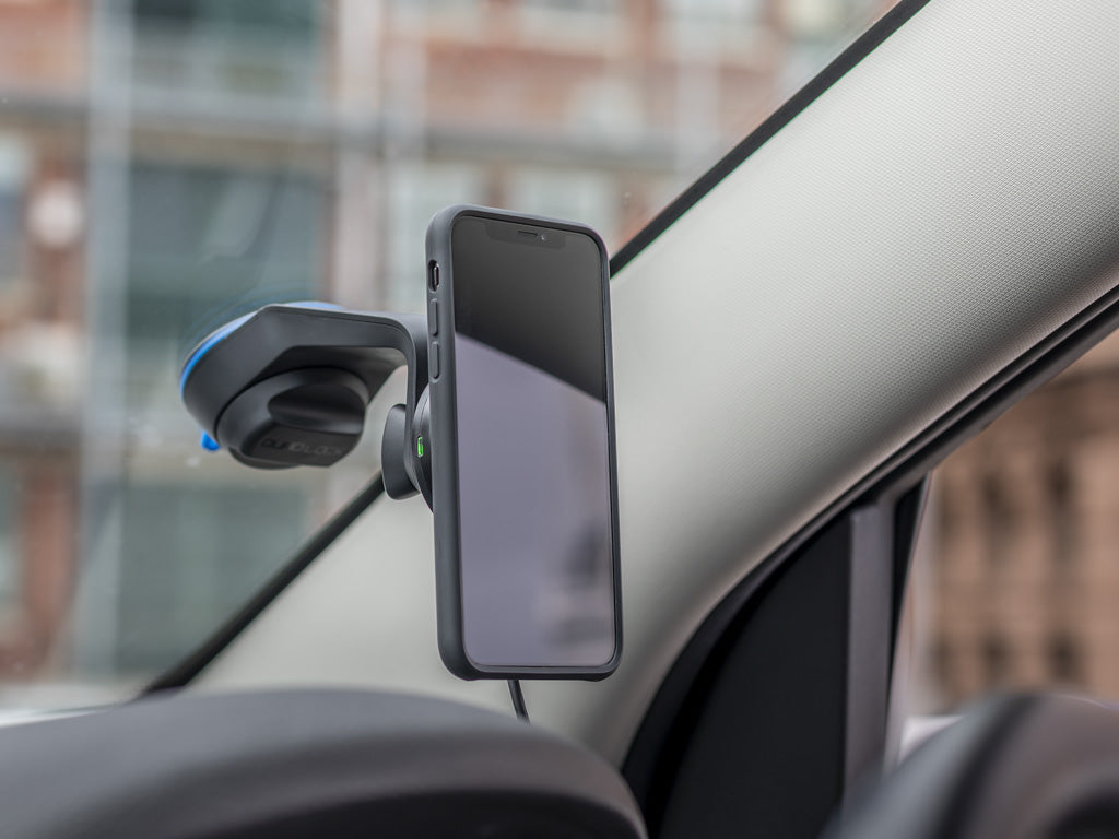 iPhone mounted to Quad Lock Wireless Charging Head on Car windscreen