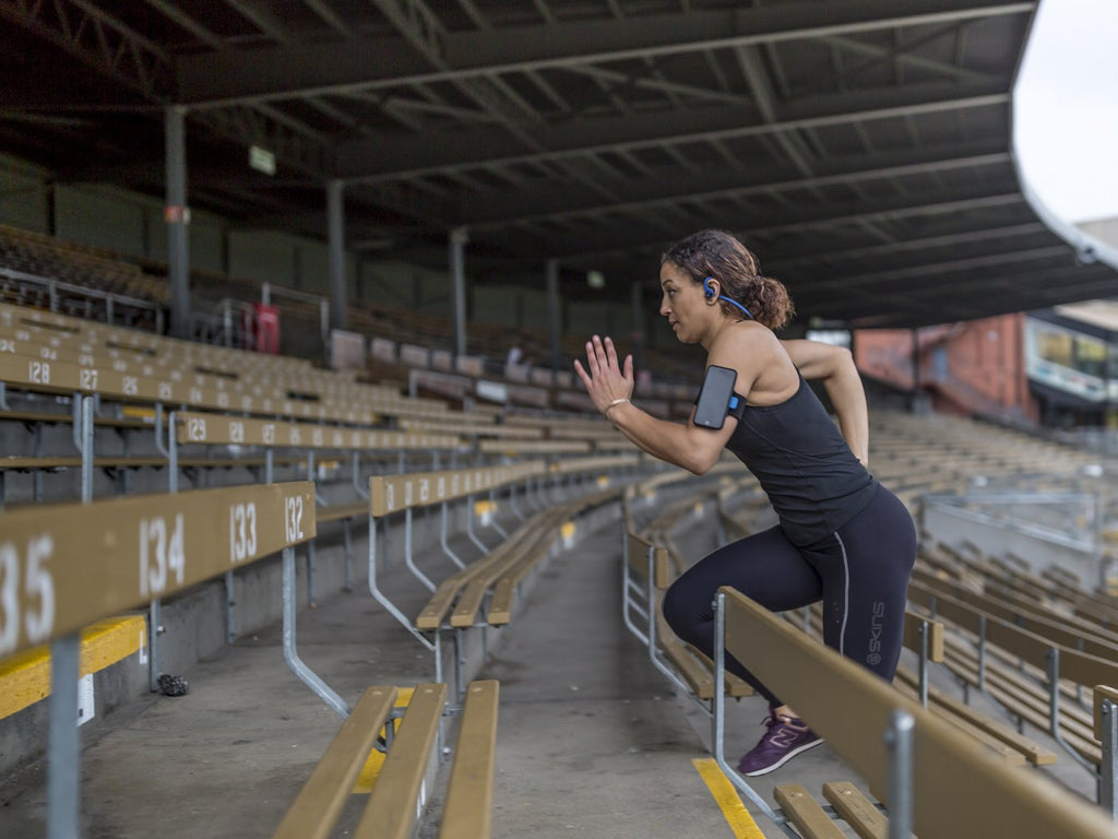 woman running upstairs with iphone sports armband