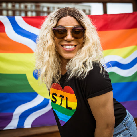 Photo of Gabby smiling, bending forward in front of a Rainbow St Louis flag.
