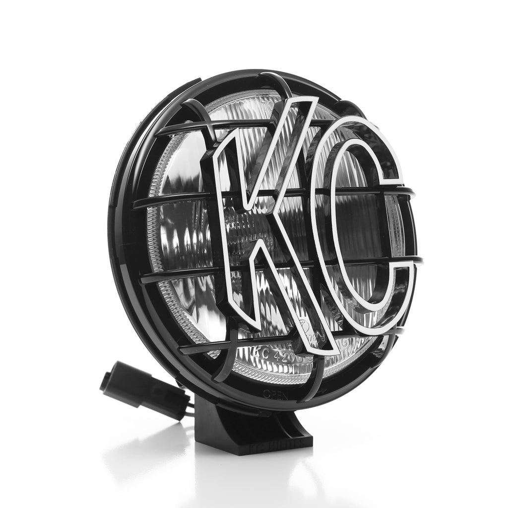 "KC's 6"" Apollo Halogen use 100W Halogen bulbs available in a spread beam pattern, slim black polymax housing and glass lens, with built in protective stone guards. Includes complete pre-terminated relay wiring harness. (151) 