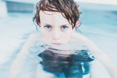 child with blue eyes in pool looking at the camera
