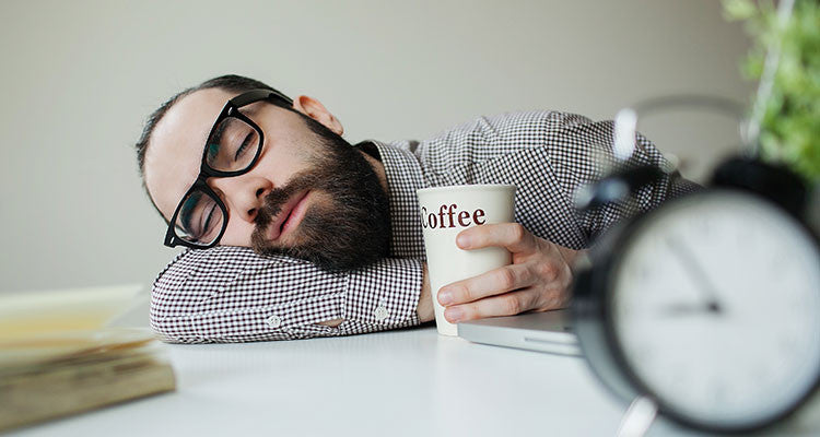 Man Taking A Caffeine Nap At His Desk With Coffee In Hand