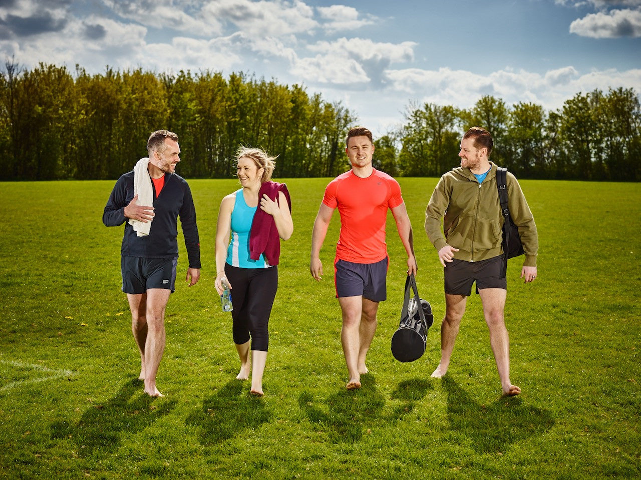Athletes walking across grass outdoor workout smiling happy