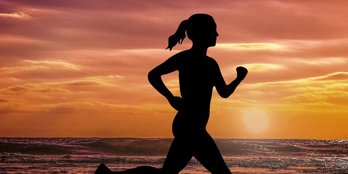 Woman running beach sunset fitness races