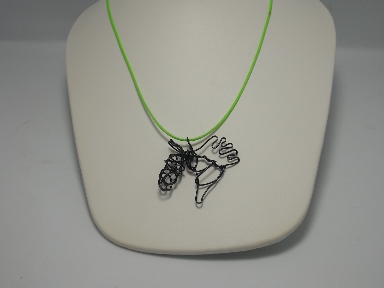 Horse head pendants on cords by Dacelle Peckler