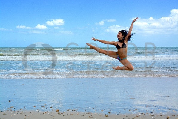 Girl kicking in the air at the beach - Colorstock™  © Anna-Rhesa Versola  - diverse stock photos