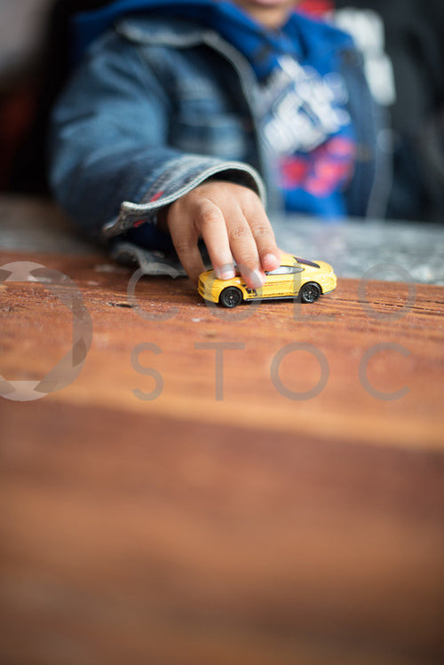 Child playing with toy car - vertical - Colorstock™  © Sirena White  - diverse stock photos