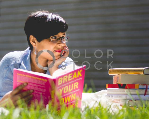 Woman reading red book in garden, Denise Benson Photography - Colorstock: diverse stock photos