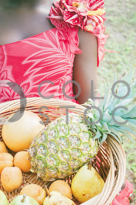 Girl holding tropical fruits in a basket