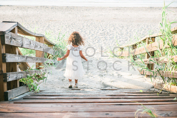 Little girl walking down the boardwalk to the beach - Colorstock™  © Sirena White  - diverse stock photos