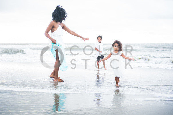 Mother and children play on the beach, in the water - Colorstock™  © Sirena White  - diverse stock photos