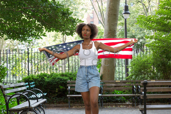 Woman walking with the American flag in the park - 2 - Colorstock™  © Click Clique NYC  - diverse stock photos