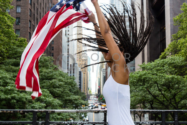 Woman unfurling the American flag in the city - 2 - Colorstock™  © Click Clique NYC  - diverse stock photos