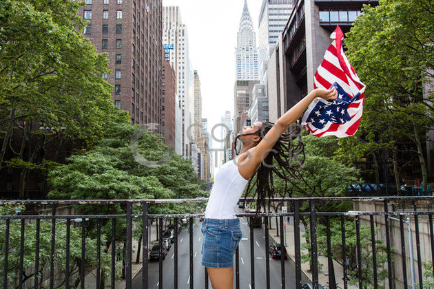 Woman waving the American flag in the city - 2 - Colorstock™  © Click Clique NYC  - diverse stock photos