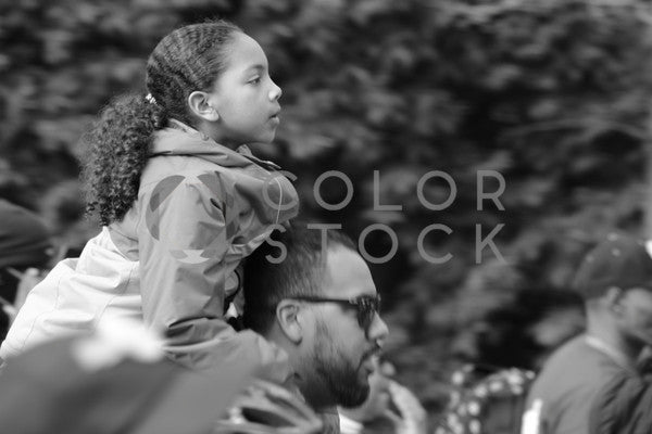 Girl sitting on dad's shoulders at a peaceful gathering - B&W