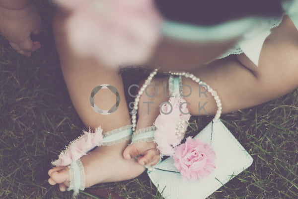 Baby's feet playing with purse, Lavish Moments Photography - Colorstock: diverse stock photos