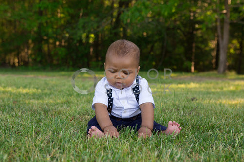 Baby seated on the grass - looking down - Colorstock™  © Jennifer Hogan  - diverse stock photos