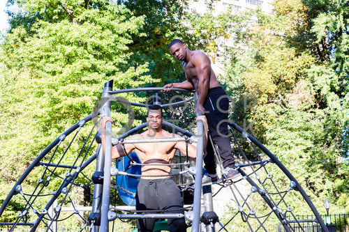 Two men exercising on a jungle gym in city park