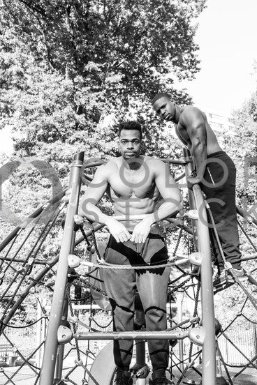 Two men exercising on a jungle gym in city park - b&w