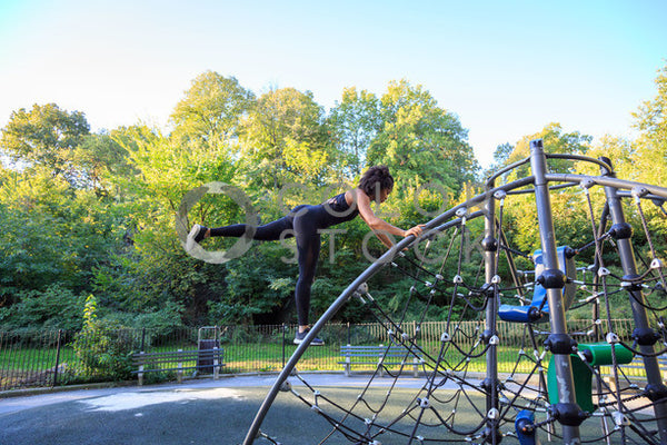 Woman exercising on a jungle gym in the park