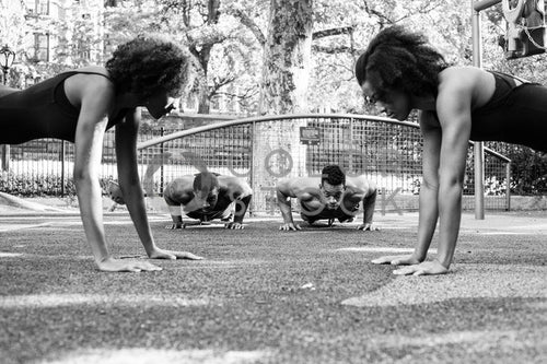 Fitness crew doing push-ups at city park