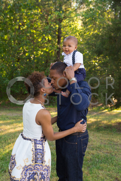 Mom and dad kissing, baby smiling - Colorstock™  © Jennifer Hogan  - diverse stock photos