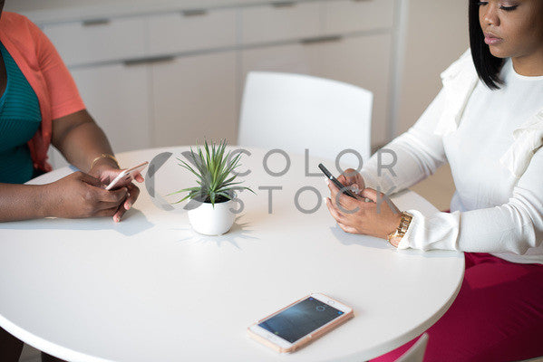 Two women checking their smartphones at a meeting, Aneris Photos - Colorstock: diverse stock photos