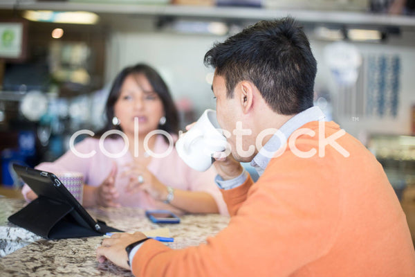 Diverse colleagues meeting at a cafe - Colorstock™  © Shea Parikh  - diverse stock photos