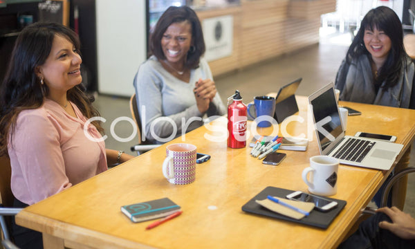 Diverse women laughing at meeting - Colorstock™  © Shea Parikh  - diverse stock photos