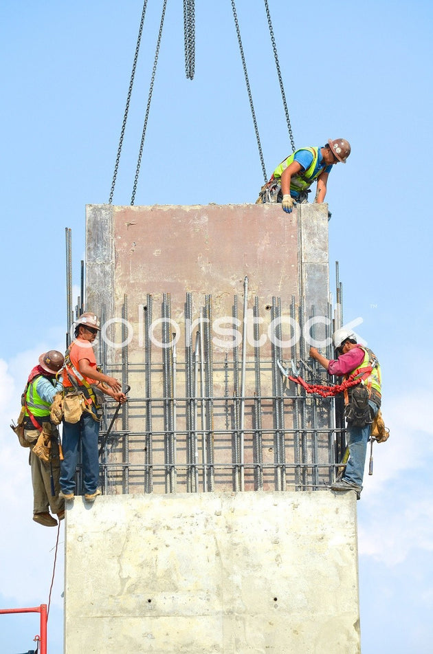 Four construction workers atop a building - Colorstock™  © David Huff  - diverse stock photos