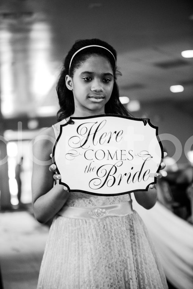 Girl holding 'here comes the bride' sign - Colorstock™  © Integrative Flash  - diverse stock photos