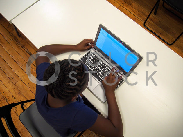 Girl looking at her laptop - overhead - Colorstock™  © Jenifer Daniels  - diverse stock photos