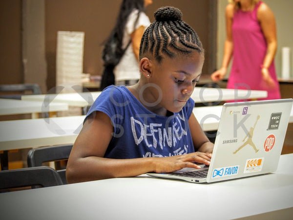 Girl using her stickered laptop in coding class - Colorstock™  © Jenifer Daniels  - diverse stock photos