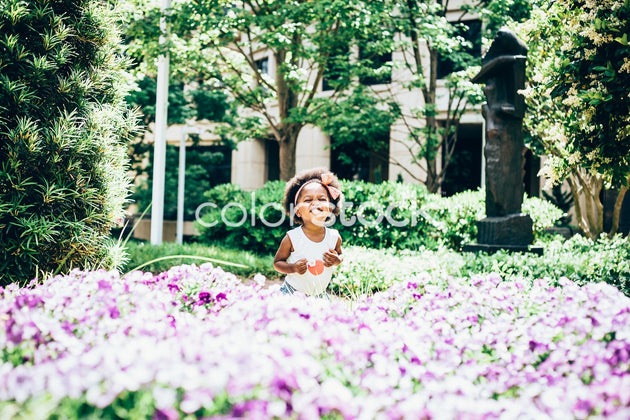 Little girl sitting in flowers - Colorstock™  © Latoya Dixon  - diverse stock photos
