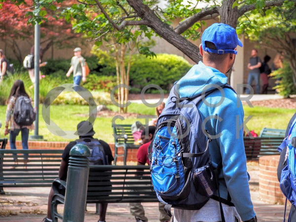 Male student walking on college campus - Colorstock™  © Jenifer Daniels  - diverse stock photos