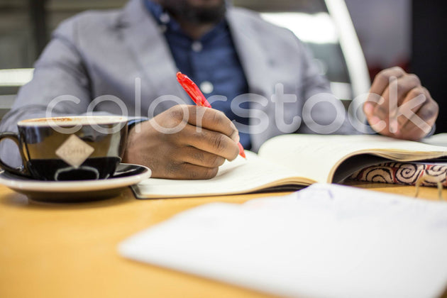Man drinking coffee and writing - Colorstock™  © Shea Parikh  - diverse stock photos