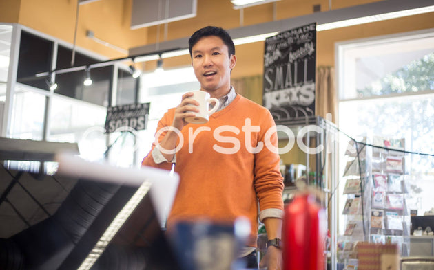 Man drinking coffee at a cafe - Colorstock™  © Shea Parikh  - diverse stock photos
