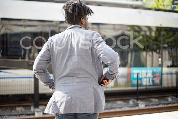 Man in city looking at train - Colorstock™  © Shea Parikh  - diverse stock photos