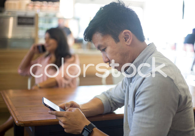 Man looking at his smartphone - Colorstock™  © Shea Parikh  - diverse stock photos
