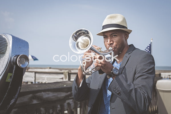 Man playing the trumpet by the beach - Colorstock™  © Latoya Dixon  - diverse stock photos