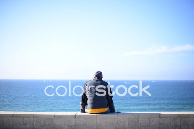 Man sitting by the waterfront - Colorstock™  © PorterhouseLA  - diverse stock photos