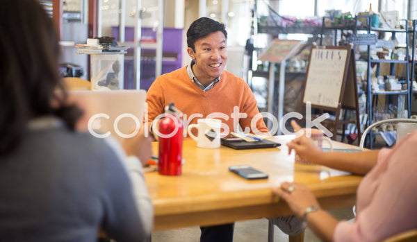 Man smiling in a meeting with colleagues - Colorstock™  © Shea Parikh  - diverse stock photos