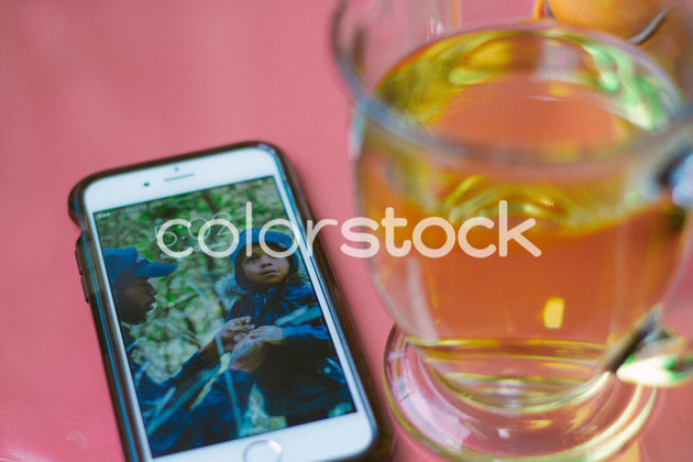 Mug of tea and smartphone with visible family on home screen - Colorstock™  © Sabrina Holder  - diverse stock photos