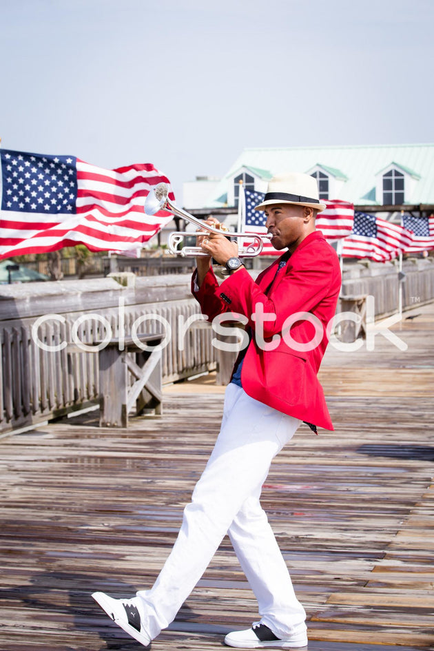 Musician playing the trumpet with American flags in the background - Colorstock™  © Latoya Dixon  - diverse stock photos