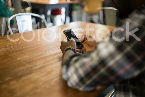 Over shoulder view of Black man on phone - Colorstock™  © Shea Parikh  - diverse stock photos