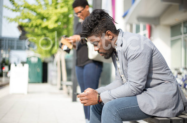 People looking at phones waiting for public transit - Colorstock™  © Shea Parikh  - diverse stock photos