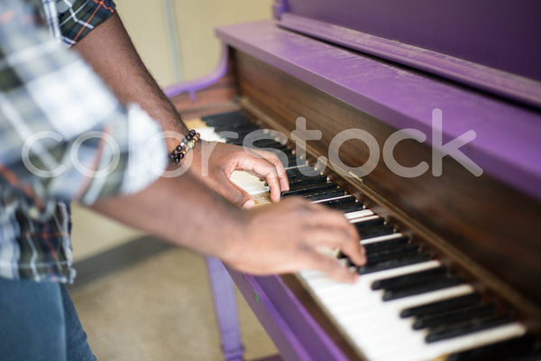 Side view of man's hands on piano keys - Colorstock™  © Shea Parikh  - diverse stock photos