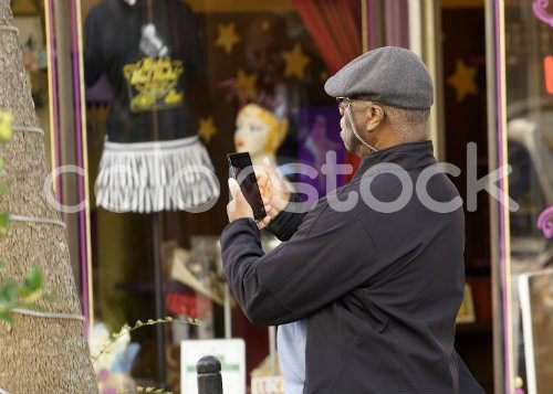 Side view of older man taking a photo with a smartphone - Colorstock™  © David Huff  - diverse stock photos