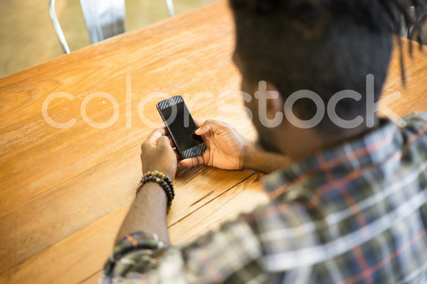 Top view of man looking at smartphone - Colorstock™  © Shea Parikh  - diverse stock photos