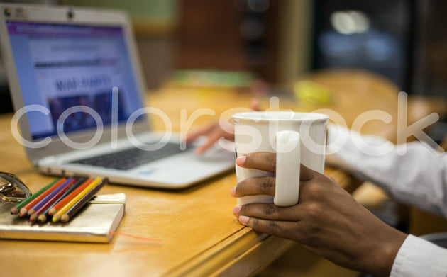 Woman holding mug and typing on a laptop - Colorstock™  © Shea Parikh  - diverse stock photos